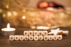 Кубы Frohe Weihnachten перед расплывчатой предпосылкой рождества Стоковое Фото