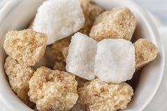 Куб тросточки белого сахара и желтого сахарного песка в белом шаре на белой предпосылке изображение наушников черноты близкое изо Стоковая Фотография RF