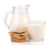 Кувшин и стекло молока с стогом crispbreads зерна изолированных на белой предпосылке Стоковое Изображение RF