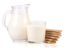Кувшин и стекло молока с стогом crispbreads зерна изолированных на белой предпосылке Стоковые Изображения RF