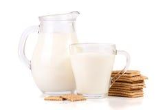 Кувшин и стекло молока с стогом crispbreads зерна изолированных на белой предпосылке Стоковое Изображение