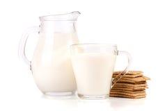 Кувшин и стекло молока с стогом crispbreads зерна изолированных на белой предпосылке Стоковая Фотография