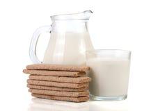 Кувшин и стекло молока с стогом crispbreads зерна на белой предпосылке Стоковое фото RF