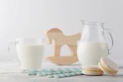 Кувшин молока и чашки с macaroons Стоковые Изображения RF
