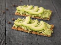 Кудрявый хлеб от пшеничной муки с сливк и кусками авокадоа на таблице Стоковые Изображения RF