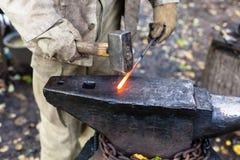 Кузнец бить молотком горячую стальную штангу молотком на наковальне Стоковая Фотография RF