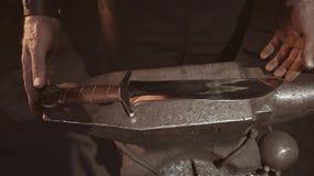 Кузнец кладет законченный выкованный нож на наковальню Конец серьезной работы Красивый продукт готов сток-видео
