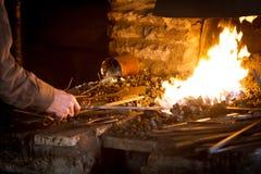 Кузнец нагревая металлический стержень Стоковые Фото