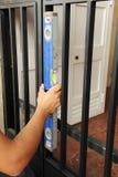 Кузнец проверяя с ровным инструментом правильное размещение входной двери металла стоковое изображение rf