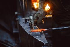 Кузнец работая на наковальне стоковое изображение