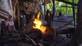 Кузнец работая с мехами кузнеца в кузнице Горячая часть металла в огне видеоматериал