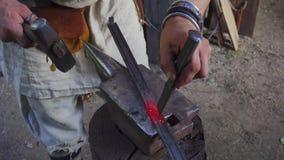 Кузнец работая с мехами кузнеца в кузнице Горячая часть металла в огне, после этого на stithy видеоматериал