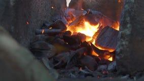 Кузнец работая с мехами кузнеца в кузнице Конец-вверх огня сток-видео