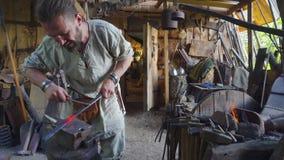 Кузнец работая с частью металла на stithy в кузнице акции видеоматериалы