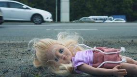 Кукла лежит около дороги с активным движением Много автомобилей приходят от позади акции видеоматериалы