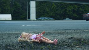 Кукла лежит около дороги с активным движением Много автомобилей приходят от позади видеоматериал