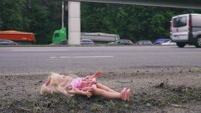 Кукла лежит около дороги с активным движением Много автомобилей приходят от позади сток-видео