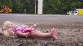Кукла падает около дороги с активным движением Много автомобилей приходят от позади движение медленное видеоматериал