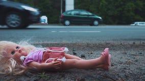 Кукла падает около дороги с активным движением Много автомобилей приходят от позади движение медленное сток-видео