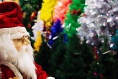Кукла Санта Клауса на различных цветах предпосылки рождественских елок Стоковая Фотография