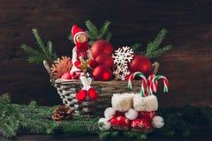 Кукла сидя в корзине с ветвями ели, красными шариками и s Стоковые Изображения