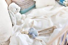 Куклы игрушки зайцев на белом листе, кровати с подушками стоковые изображения