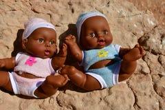 Куклы мальчика играют в песке и сидят на скалистой горе в пустыне Стоковые Изображения RF