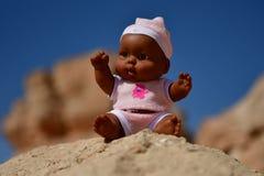 Куклы мальчика играют в песке и сидят на скалистой горе в пустыне Стоковая Фотография