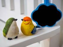 Куклы птицы сделанные из штукатурки на белой предпосылке стула с малой доской заволакивают Стоковые Фото