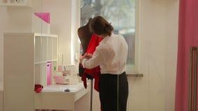 Кукла создателя одежд модельера задрапировывая в студии Модельер, портной, dressmaker регулируя одежды сток-видео