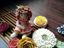 Кукла среди цветков Стоковое Изображение