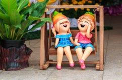 Куклы глины мальчика и девушки в деревянных качаниях Стоковая Фотография