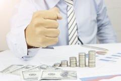 Кулак выставки бизнесмена к уверенному и успех в деле на таблице с деньгами, бумагой работы и монетками, концепцией как уверенный стоковое изображение rf