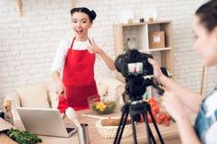 2 кулинарных блоггера прочитали от компьтер-книжки с одной девушкой за камерой Стоковое фото RF