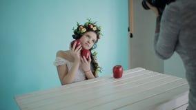Кулуарная съемка во время крытого photoshoot Фотограф женщины работает с молодой моделью в образе весны с плодоовощ внутри сток-видео
