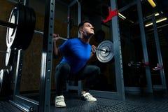 культурист в голубой футболке с штангой в спортзале Стоковая Фотография RF