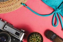 Купальник, шляпа, автомобиль игрушки, солнечные очки, камера, кактус на розовой предпосылке Концепция перемещения взгляд сверху с Стоковые Изображения