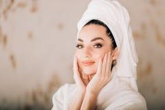 Купальный халат и полотенце привлекательной девушки нося белый на голове в bathroom стоковое изображение rf