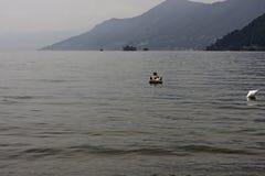 Купальщик ослабляет путем плавать с раздувным тюфяком на Стоковое Изображение