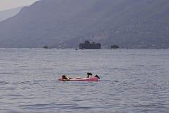 Купальщик ослабляет путем плавать с раздувным тюфяком на стоковая фотография rf