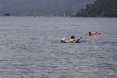 Купальщик ослабляет путем плавать с раздувным тюфяком на Стоковое Фото