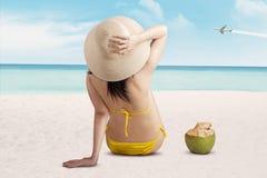 Купальник женщины нося сидя на пляже Стоковые Фотографии RF