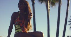 Купальник сексуальной женщины нося сидя на стенде Стоковые Фото