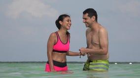 Купальные костюмы молодых пар нося имея потеху в океане сток-видео