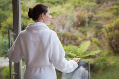 Купальный халат женщины нося против запачканных заводов Стоковое фото RF