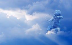 Купидон с стрелкой над облачным небом Стоковое фото RF