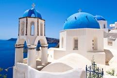 Куполы православных церков церков Oia и колокольня santorini острова холма Греции зданий Стоковое Фото