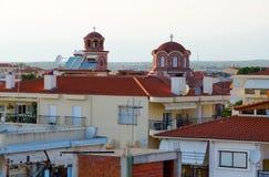 Куполы церков St Paraskeva среди традиционных греческих зданий низко-подъема, Nea Kallikratia, Греции стоковое изображение rf