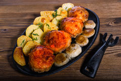 Куриные котлеты с зажаренными в духовке кусками картошек и грибов в старом skillet Стоковые Изображения