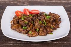 Куриные печени в сметанообразном соусе с луком на белой плите Стоковые Фото